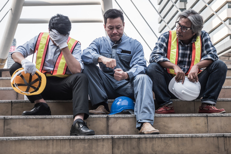 Photo pour Unhappy engineer sitting on building stairs at construction site, They feel tired and stressed from work. - image libre de droit