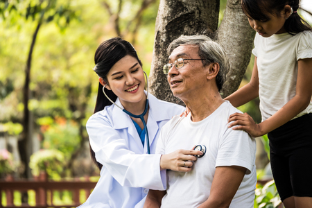 Foto de Young female doctor using the stethoscope listen to elderly patient heartbeat in hospital garden - Imagen libre de derechos