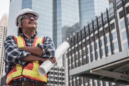 Foto de Architect or civil engineer holding building's blueprint with construction site background. - Imagen libre de derechos
