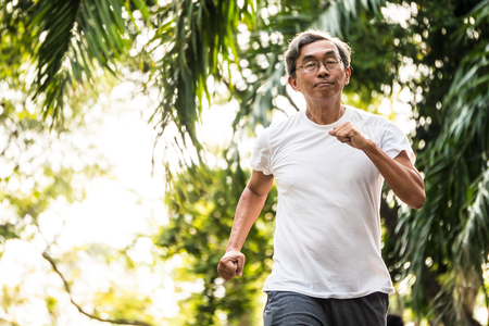 Photo pour Senior asian man jogging in a park. Healthcare concept - image libre de droit
