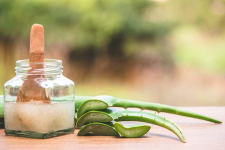Foto de Fresh aloe vera and jelly in glass bottle on wooden table with nature background - Imagen libre de derechos