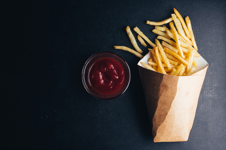 Photo for Top view of French fries with ketchup on black background. copy space - Royalty Free Image