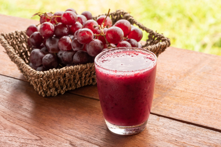 Photo pour Glass of Grape juice smoothie on wooden table - image libre de droit