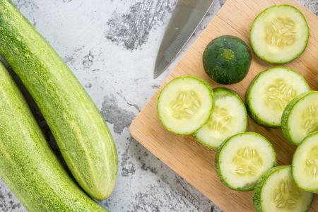 Photo pour Fresh cucumber slices on a cutting board. Top view - image libre de droit