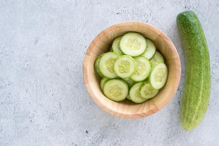 Foto de Fresh cucumber slices on a wooden bowl. Top view - Imagen libre de derechos