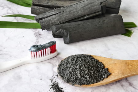 Foto de Toothpaste by activated charcoal powder on marble table - Imagen libre de derechos