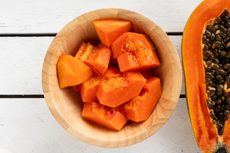 Photo for Slices of sweet papaya in wooden bowl on wooden table. - Royalty Free Image