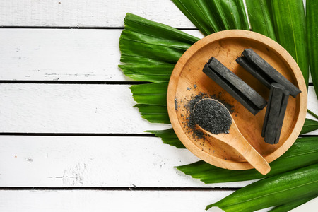 Photo for Bamboo charcoal and powder on wooden table. copy space - Royalty Free Image