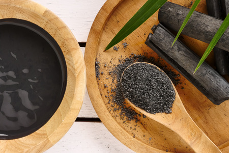 Photo for Facial mask and scrub by activated charcoal powder on wooden table - Royalty Free Image