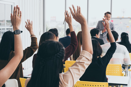 Photo for Audience raising hands up while businessman is speaking in training at the office. - Royalty Free Image