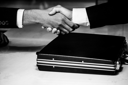 Photo pour Business man giving something in a briefcase while give success the deal to finishing contract agreement - image libre de droit
