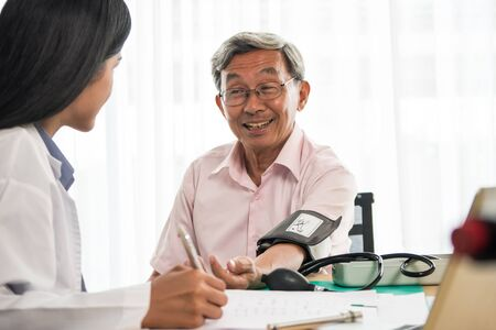 Foto per Doctor measuring blood pressure of elderly man in medical office - Immagine Royalty Free