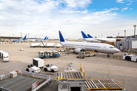 Photo pour A fleet of commercial aircrafts being serviced at the terminal of an international airport. - image libre de droit