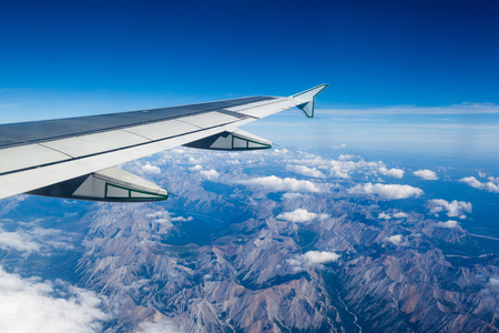 Foto de Airplane window view showing wing of plane flying over clouds and Rocky Mountains. - Imagen libre de derechos