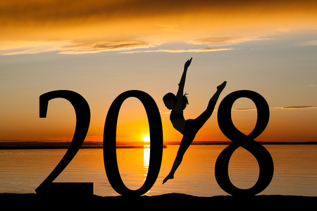 Photo for 2018 New Year silhouette of a girl dancing or exercising at the beach during golden sunrise or sunset with copy space. - Royalty Free Image