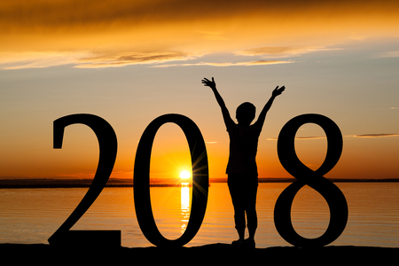 Foto de 2018 New Year silhouette of a girl with hands raised at the beach during golden sunrise or sunset with copy space. Concept of joy, praise, worship, connection with nature. - Imagen libre de derechos