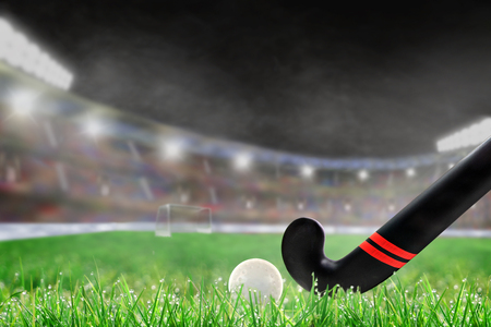Foto de Field hockey stick and ball on grass in brightly lit outdoor stadium with focus on foreground and shallow depth of field on background. Deliberate lens flare and copy space. - Imagen libre de derechos