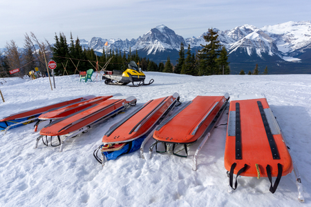 Foto de Rows of ski patrol toboggans or rescue sleds lie on snow on mountain ski resort. Also known as akia or emergency rescue sledg, it is used by mountain rescue teams in winter to evacuate an injured skier or snowboarder. - Imagen libre de derechos