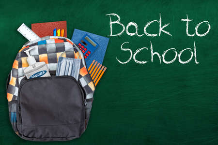 Photo pour Back to school education concept in the new normal during Covid-19 pandemic with backpack stuffed with stationery, hand sanitizer and face mask on chalkboard background. - image libre de droit