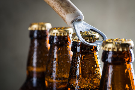 Foto de Brown ice cold beer bottles with water drops and old opener - Imagen libre de derechos