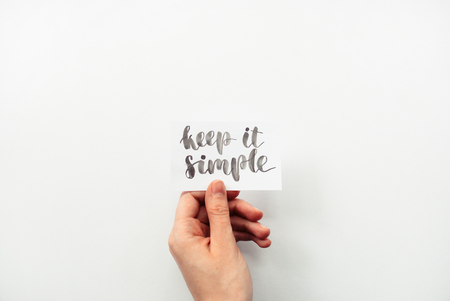 Photo for Minimal composition on a white background with girl's hand holding card with inspirational quote keep it simple written in calligraphy style - Royalty Free Image