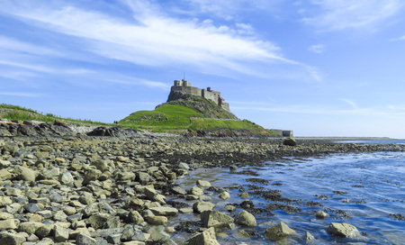 Photo pour Lindisfarne Castle panoramic view from a rock beach and blue water, Holy Island, Northumberland, UK - image libre de droit