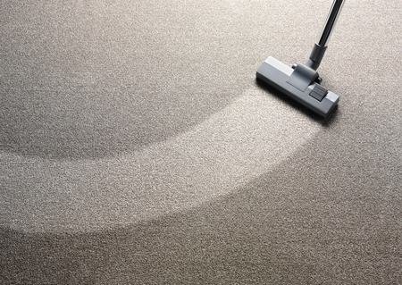 Photo pour Vacuum cleaner on a carpet with an extra clean strip for copy space - image libre de droit