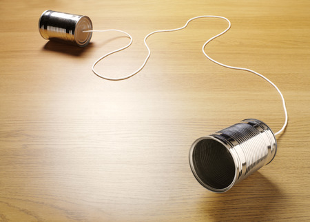 Foto de Two tin cans joined with a cord on a wooden background for primitive communication - Imagen libre de derechos