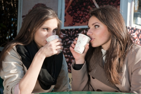Two women having coffee in take-away and chatting
