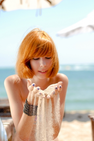 Young beautiful redhead woman model in bikini on sea coast hands full of sand on sunny summer day