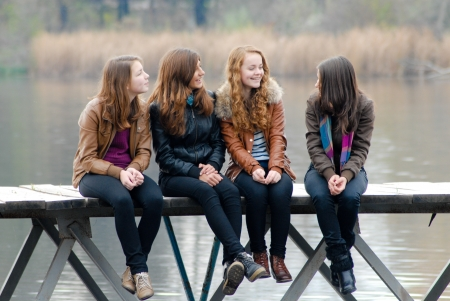 Four happy school girls sitting on river bridge on autumn day and looking away