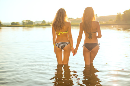 Foto de filtered image of 2 attractive young women or teenage girls best friends in bikini holding hands and looking at summer river or lake on outdoors copy space background - Imagen libre de derechos