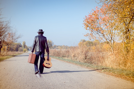 Photo for Young man musician in retro hat and leather jacket with vintage suitcase and guitar walking away on empty autumn road copy space background - Royalty Free Image