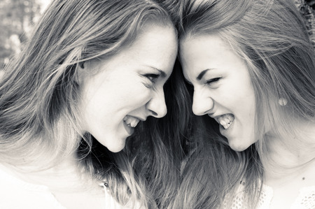 Closeup picture of two beautiful young ladies looking and roaring at each other