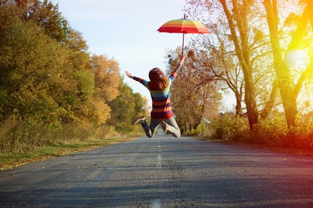 Foto de Conceptual picture of jumping lady holding umbrella with arms sideways on empty country road in autumn - Imagen libre de derechos