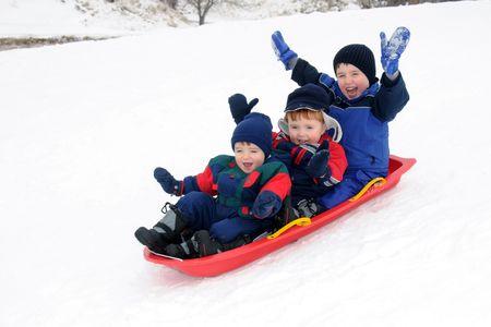 Three preschool-aged boys have fun together sliding downhill on a pleasant winter day.