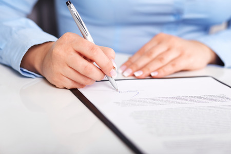 Photo pour Young woman signs a contract on a white table - image libre de droit