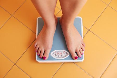 Foto de A pair of female feet standing on a bathroom scale - Imagen libre de derechos