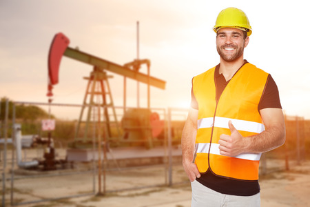 Photo pour Refinery worker standing in front of the oil pump - image libre de droit