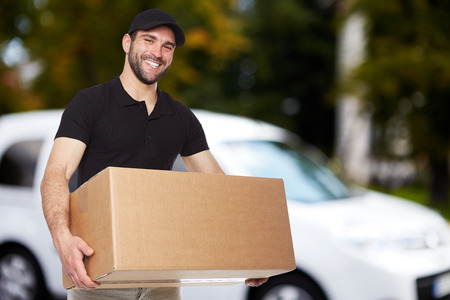 Photo pour Smiling delivery man holding a paper box - image libre de droit