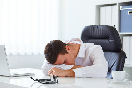 Photo pour Young businessman in white shirt sleeping on desk in the office - image libre de droit