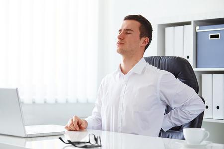 Foto de Young businessman has backache at work with a laptop - Imagen libre de derechos
