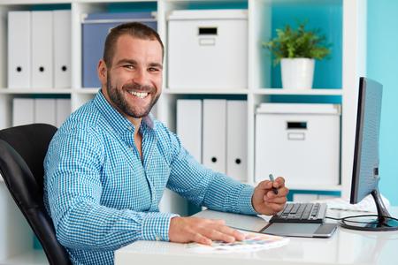 Foto de Happy graphic designer working on digital tablet - Imagen libre de derechos