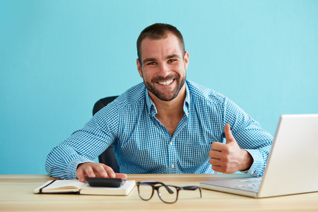 Photo pour Smiling businessman calculates taxes and gesturing thumbs up - image libre de droit