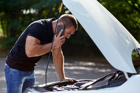 Foto de Man calling someone for help with his broken car - Imagen libre de derechos