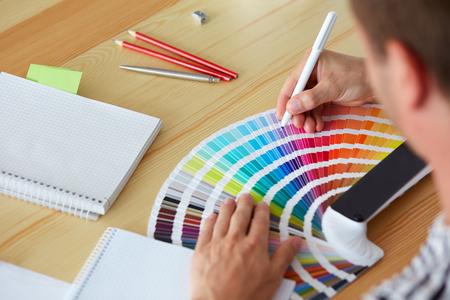 Foto de Graphic designer choosing a color from the sampler - Imagen libre de derechos