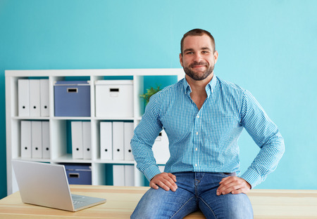 Foto de Young businessman sitting on desk in office - Imagen libre de derechos