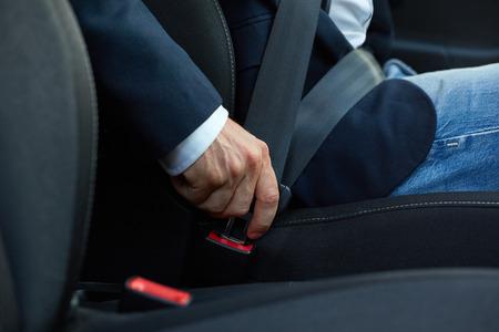 Photo pour Driver sits in the car and fastens his seat belt - image libre de droit