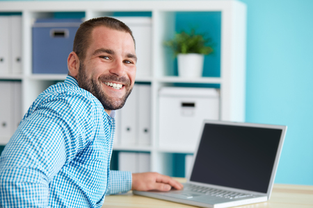 Foto de Happy businessman working in modern office on computer - Imagen libre de derechos