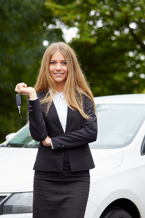 Young business woman with car key in hand